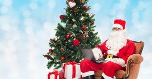 圣诞老人服装的人有膝上型计算机的 免版税库存照片