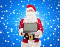 圣诞老人服装的人有膝上型计算机的 免版税图库摄影