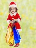 圣诞老人服装的小女孩有五颜六色的包裹的 库存图片