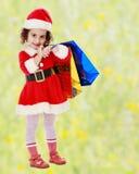 圣诞老人服装的小女孩有五颜六色的包裹的 免版税图库摄影