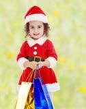 圣诞老人服装的小女孩有五颜六色的包裹的 库存照片