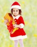 圣诞老人服装的小女孩有礼物的 免版税库存照片