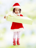 圣诞老人服装的小女孩有礼物的 免版税库存图片