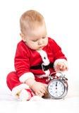 圣诞老人服装的小男孩有闹钟的 免版税库存图片