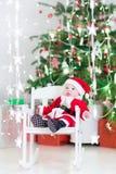圣诞老人服装的微笑的新出生的男婴在圣诞树下 免版税库存照片