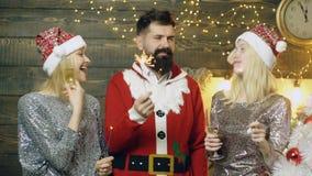 圣诞老人服装的有胡子的人和新年的帽子的两个女孩喝香槟和烧伤闪烁发光物光,庆祝 股票录像