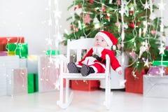 圣诞老人服装的逗人喜爱的新出生的男婴在圣诞树下 库存图片