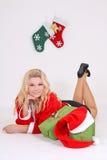 圣诞老人服装的金发碧眼的女人与礼品 免版税库存照片