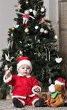 圣诞老人服装的婴孩在装饰与玩具的圣诞树附近坐 图库摄影