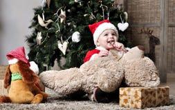 圣诞老人服装的婴孩在装饰与玩具的圣诞树附近坐 免版税库存照片