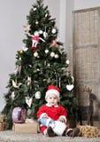 圣诞老人服装的婴孩在装饰与玩具的圣诞树附近坐 免版税库存图片