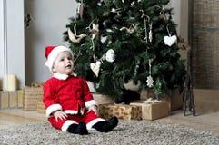 圣诞老人服装的婴孩在装饰圣诞树附近坐 库存照片