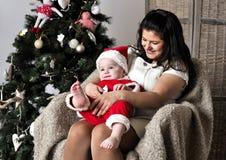 圣诞老人服装的婴孩有母亲的坐椅子在圣诞树附近 库存照片