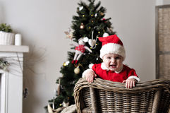 圣诞老人服装立场的婴孩在圣诞树附近的椅子 库存图片