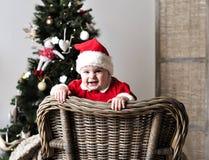 圣诞老人服装立场的婴孩在圣诞树附近的椅子 库存照片