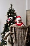圣诞老人服装立场的婴孩在圣诞树附近的椅子 免版税库存照片