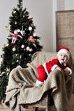 圣诞老人服装立场的婴孩在圣诞树附近的椅子 免版税图库摄影
