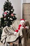 圣诞老人服装立场的婴孩在圣诞树附近的椅子 免版税库存图片