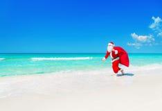 圣诞老人沿与圣诞节礼物大袋的海洋海滩跑 库存照片