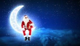 圣诞老人照片坐月亮 免版税库存照片