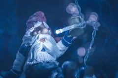 圣诞老人玩具欢呼在蓝色被定调子的颜色的冷的冬天圣诞夜与在背景的被弄脏的街灯 库存图片