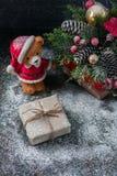 圣诞老人玩具熊,礼物盒包裹了亚麻布和装饰用绳子,在棕色葡萄酒木板backg的圣诞节装饰 免版税库存图片