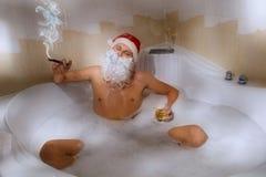 圣诞老人用坐在浴盆的威士忌酒和雪茄 库存照片