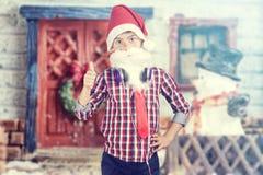 圣诞老人男孩佩带的耳机 免版税库存图片