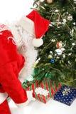 圣诞老人留下礼物在圣诞树下 免版税库存照片