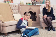 给圣诞老人的一封男孩文字信件与他母亲和她 免版税库存图片