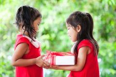 圣诞老人的两个逗人喜爱的亚裔儿童女孩穿戴拿着圣诞节礼物 图库摄影
