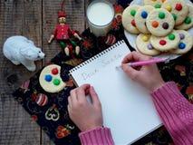 圣诞老人的信件和在木背景的彩虹曲奇饼 免版税库存图片