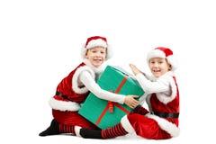 圣诞老人的可爱的愉快的笑的男孩给拿着圣诞节礼物盒穿衣 查出的空白背景 免版税图库摄影