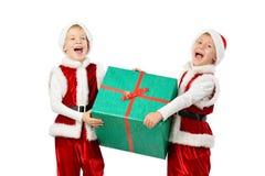 圣诞老人的可爱的愉快的笑的男孩给拿着圣诞节礼物盒穿衣 查出的空白背景 库存图片