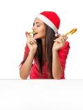 圣诞老人的帮手帽子的美丽的女孩吃棒棒糖的 免版税库存图片