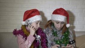 圣诞老人的帽子的两滑稽的女孩拜访电话 他们坐有圣诞节闪亮金属片的长沙发在他们 股票录像