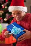 圣诞老人的帽子的人得到了礼物 免版税库存照片