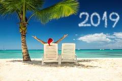 圣诞老人的帽子的新年2019年和妇女在热带海滩 库存照片