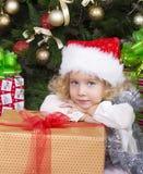圣诞老人的帽子的逗人喜爱的小女孩有大圣诞节礼物的 免版税库存照片