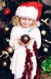 圣诞老人的帽子的逗人喜爱的小女孩装饰圣诞树的 库存照片