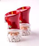 以圣诞老人的形式两个蜡烛白色木backgound的 库存图片