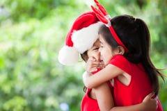 圣诞老人的愉快的两个亚裔儿童女孩穿戴拥抱 免版税库存照片