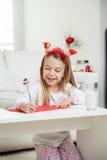 给圣诞老人的愉快的女孩文字信件 免版税库存照片