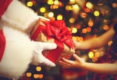 圣诞老人的手给孩子圣诞节礼物 免版税库存照片