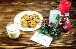 圣诞老人的曲奇饼和牛奶 接近款待是三个蜡烛和一张卡片的装饰与笔记 库存照片