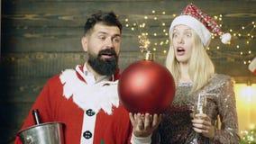 圣诞老人的服装和一个白肤金发的女孩的有胡子的人有举行在他们的一颗灼烧的炸弹的手上的吃惊的面孔的 新 影视素材