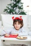 给圣诞老人的男孩佩带的头饰带文字信件 免版税库存照片