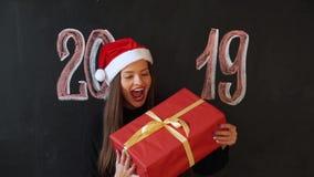圣诞老人的盖帽的年轻女人在与题字的板岩墙壁背景2019年 女孩微笑,她将是愉快的 影视素材