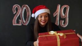 圣诞老人的盖帽的年轻女人在与题字的板岩墙壁背景2019年 女孩微笑,她将是愉快的 股票录像