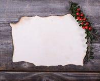 圣诞老人的空的纸笔记用在木后面的红色莓果 图库摄影